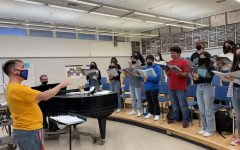 """Choir director Jeffery Fahey conducts Prestige, or production choir, as they rehearse """"Feed the Birds"""" for their Fall concert. Photo by Elias Robles."""